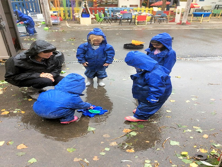 Nursery children playing outside in the wet weather
