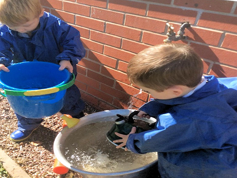 Children filling buckets of water