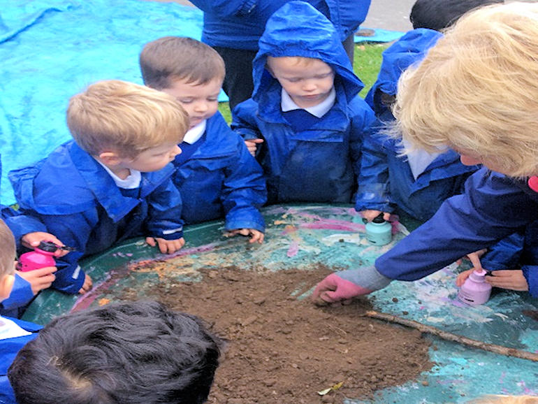 Children learning about soil at Forest School