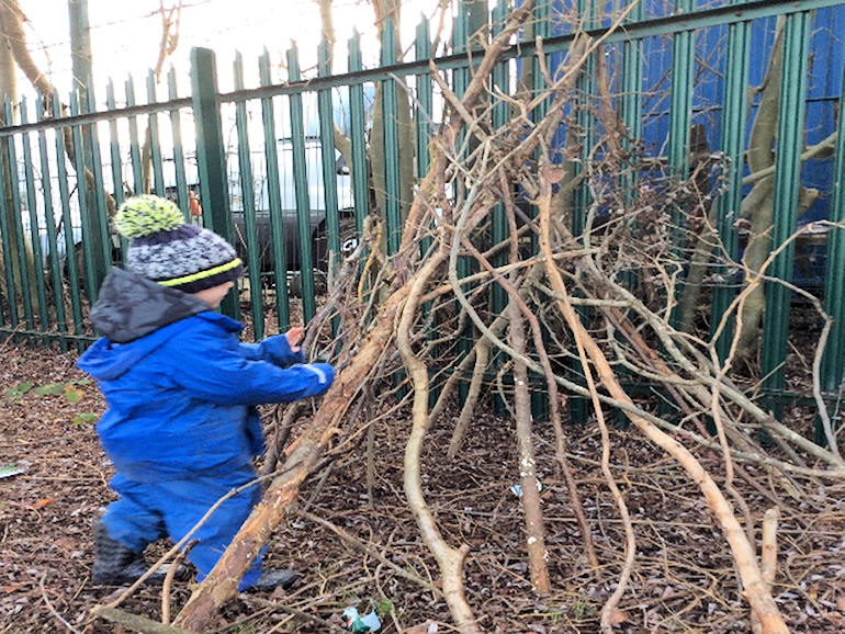 A child building a shelter with tree branches